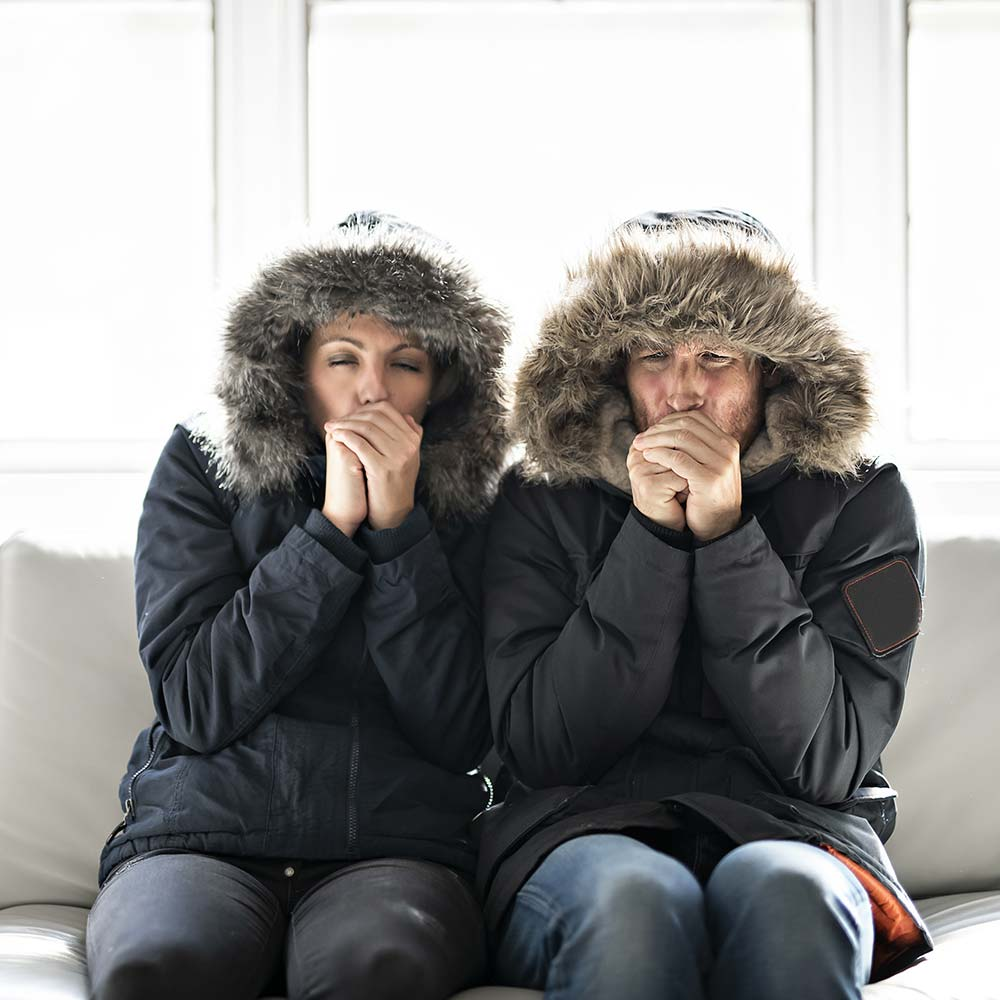An unhappy couple wearing winter coats sitting on a couch