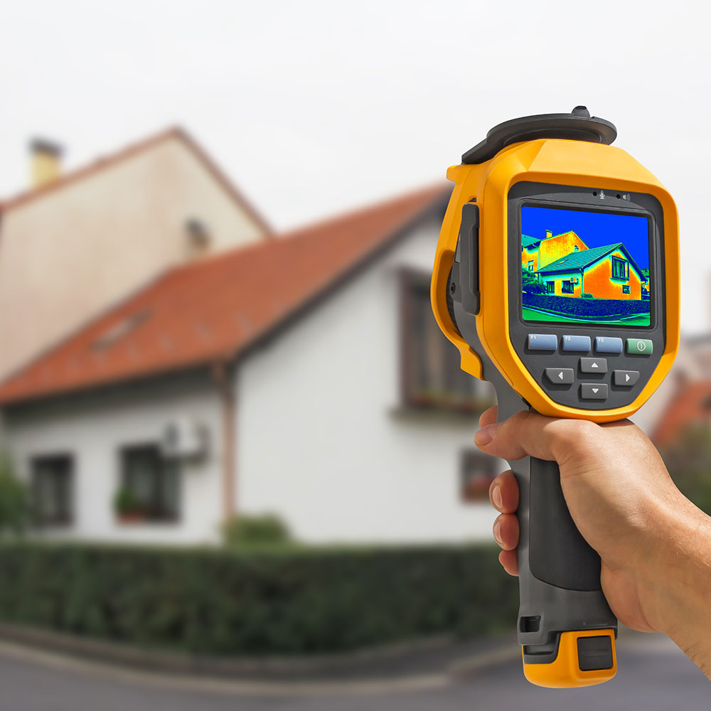 house exterior. A hand holding an infrared sensor toward the house.  The sensor screen shows colors indicating heat loss from areas of the house.